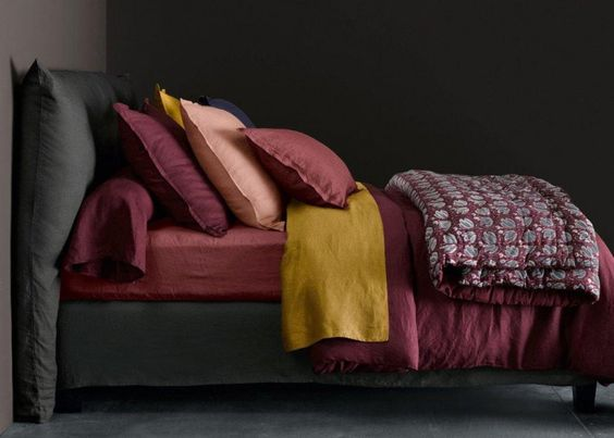 chambre noire avec du linge de lit bordeaux et des coussins moutarde