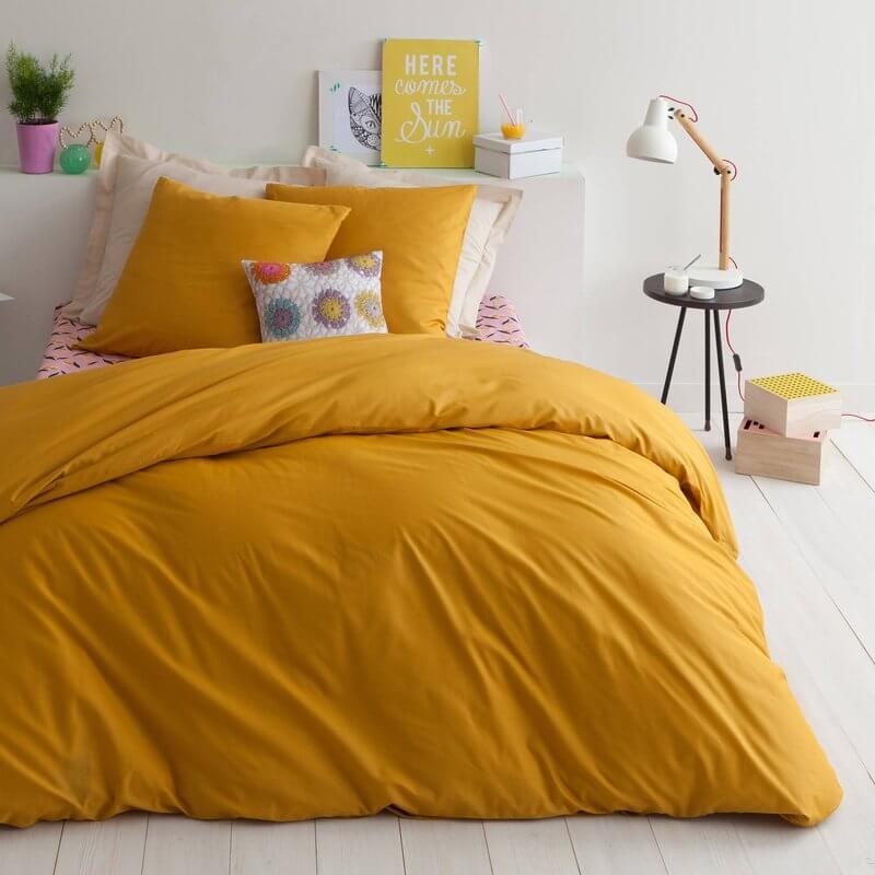 chambre avec du linge de lit couleur moutarde