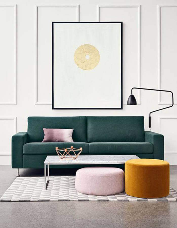 salon avec un canapé vert et un pouf couleur moutarde