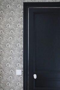 Zoom porte noir et papier peint
